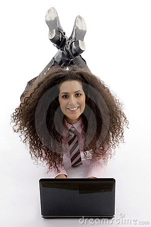 Smart young businesswoman lying down with laptop