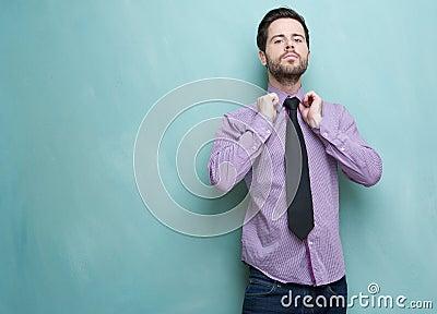 Smart young guy adjusting his necktie