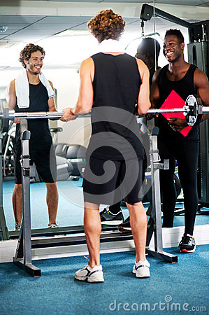 Smart young guy lifting barbells in gym