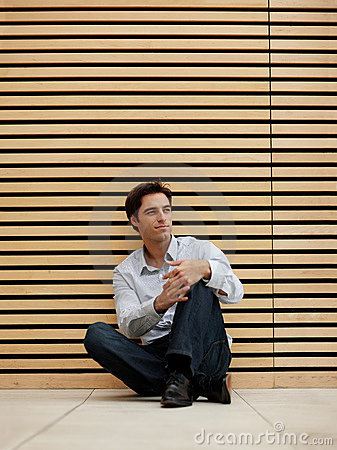 Smart young man sitting on floor and looking away
