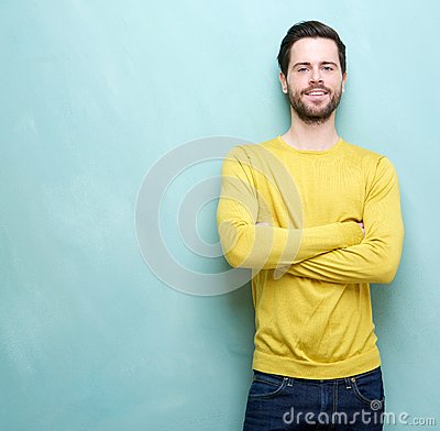 Smart young man in yellow shirt smiling with arms crossed