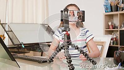 Smartphone op een driepoot die het jonge meisje spreken filmen stock video