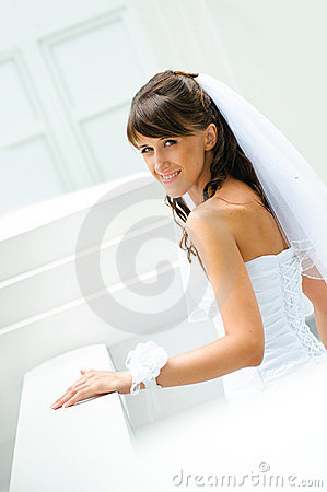 Smiles bride with a veil on white outdoor backgro