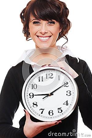 Smiley businesswoman holding clock