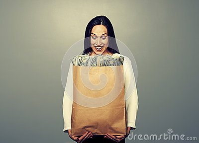 Smiley businesswoman holding paper bag
