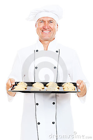 Smiley cook holding baking tray with cookies