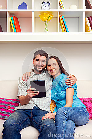 Couple sitting on sofa and holding the tablet pc