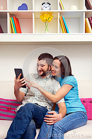 Smiley couple sitting on sofa