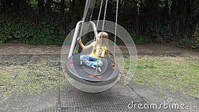 Smiley Girl Swinging Outdoor feliz, niño que juega en los niños 4K del parque del patio metrajes