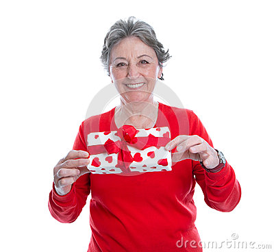 Smiley grey haired woman in red holding present isolated on whit