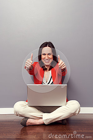 Woman with laptop giving thumbs up