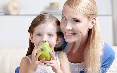 Smiley mom with her eating apple daughter