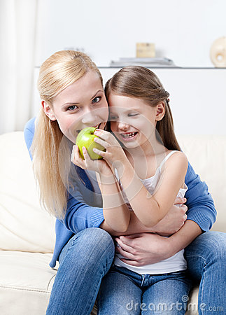 Smiley mother with her eating apple daughter