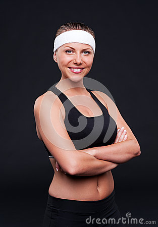 Smiley sportswoman over dark background