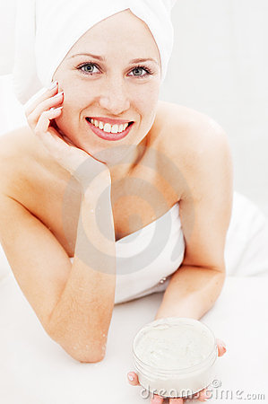 Smiley woman with face cream after shower
