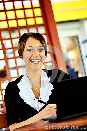 Smiley woman using laptop at the cafe