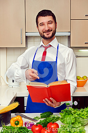 Smiley young man pointing at the cookbook