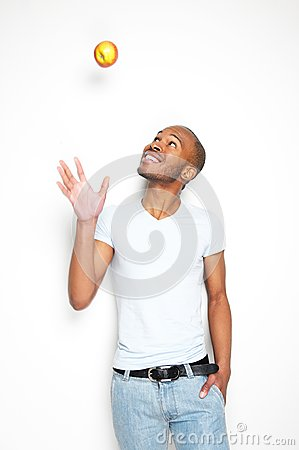 Free Smiling African American Man Throwing An Apple In The Air Royalty Free Stock Image - 31500636