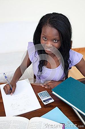 Smiling Afro-American teen girl doing her homework