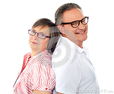 Smiling aged couple posing back to back