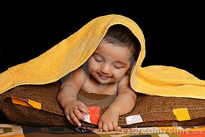 Smiling Asian baby girl under yellow towel