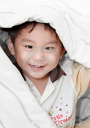 Smiling asian boy covered by blanket