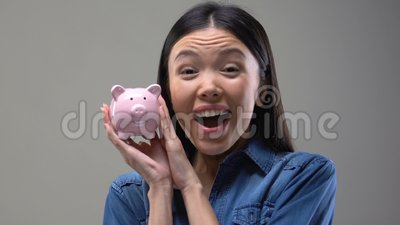 Smiling Asian lady shaking piggy bank, money saving tips, finance and budget. Stock footage stock video