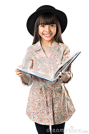 Smiling asian little girl with a book in hand