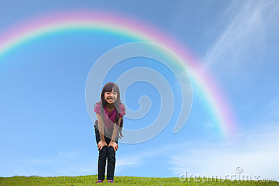 Smiling asian little girl standing on green grass under the rain
