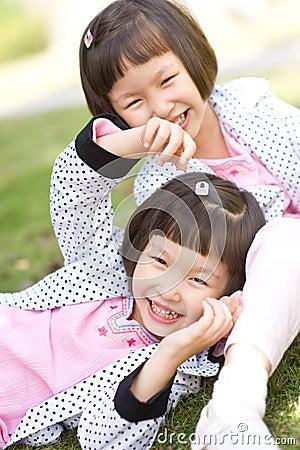 Smiling asian twin girls