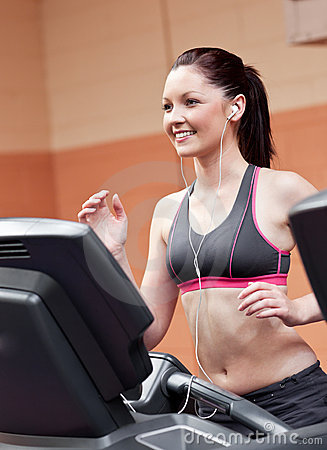 Smiling athletic woman training on a treadmill