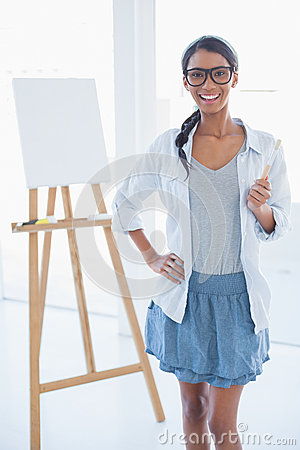 Smiling attractive artist holding paintbrush