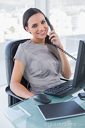 Smiling attractive businesswoman answering phone