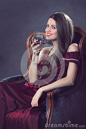 Smiling attractive woman poses with a glass of red wine