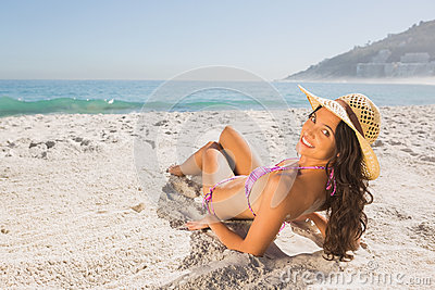 Smiling attractive young woman in pink bikini sunbathing