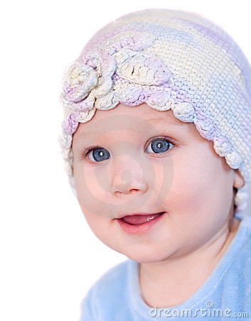Smiling baby girl showing teeth wearing a  hat