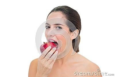 Smiling bare brunette eating red apple
