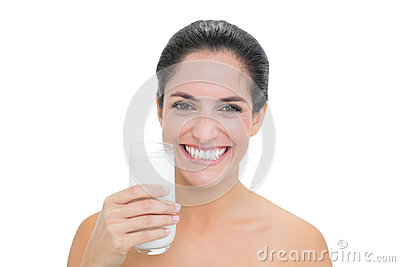 Smiling bare brunette holding glass of milk