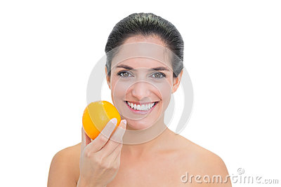 Smiling bare brunette holding orange