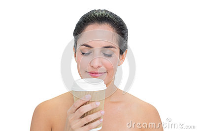 Smiling bare brunette smelling disposable cup