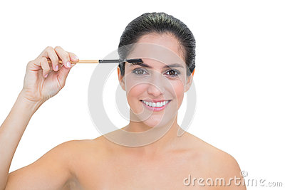 Smiling bare brunette using eyebrow brush