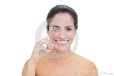 Smiling bare brunette using eyelash curler