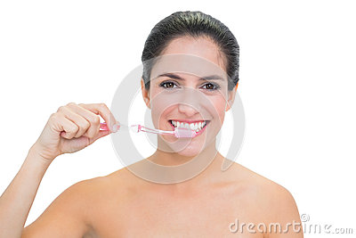 Smiling bare brunette using toothbrush