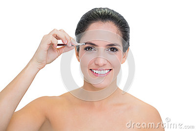 Smiling bare brunette using tweezers