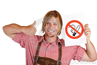 Smiling Bavarian man holds no-smoking-rule sign
