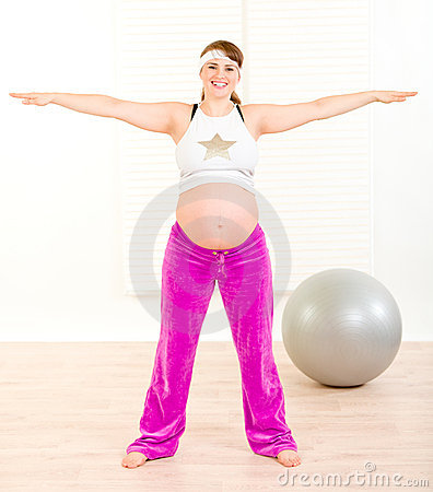 Smiling beautiful pregnant female doing exercise