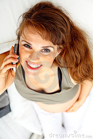 Smiling beautiful pregnant female talking phone.