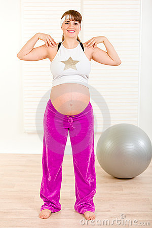Smiling beautiful pregnant woman doing exercise