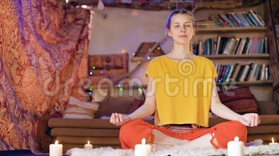 young man sits in lotus position on top looks down