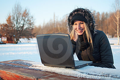 Smiling beautiful young woman with laptop sitting